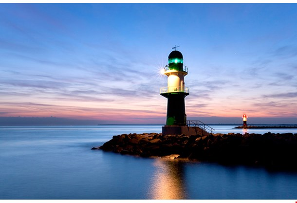 Lighthouse At Sunset At The Baltic Sea Harbor Entrance Of Rostock