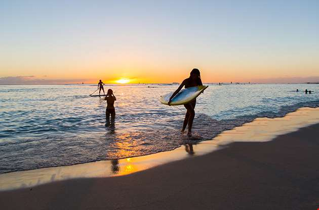 Surfboard Rider In The Sunset Of Waikiki Beach On Oahu Hawaii-Surfboard Rider In The Sunset Of Waikiki Beach On Oahu Hawaii