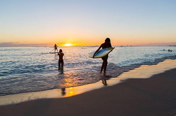 Surfboard Rider In The Sunset Of Waikiki Beach On Oahu Hawaii